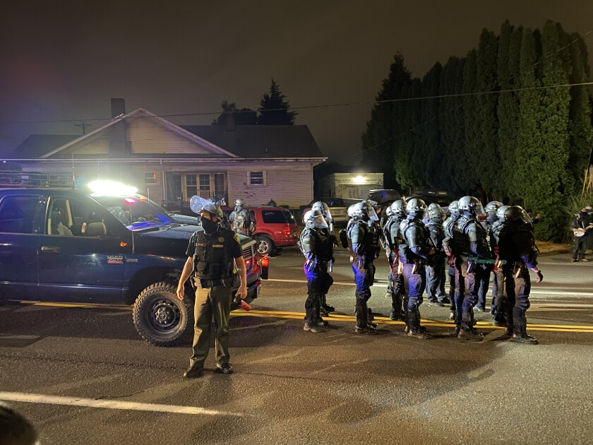 Multnomah County sheriff's deputies in Portland line up to clear protesters off a street.
