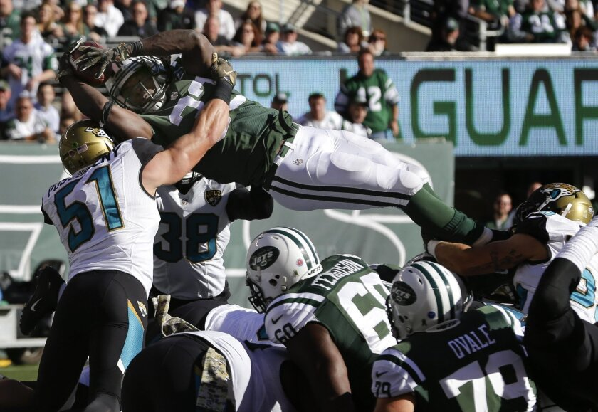 New York Jets running back Chris Ivory (33) is stopped at the goal line by Jacksonville Jaguars middle linebacker Paul Posluszny (51) as he attempts to dive over the defensive line during the first quarter of an NFL football game, Sunday, Nov. 8, 2015, in East Rutherford, N.J. (AP Photo/Seth Wenig)