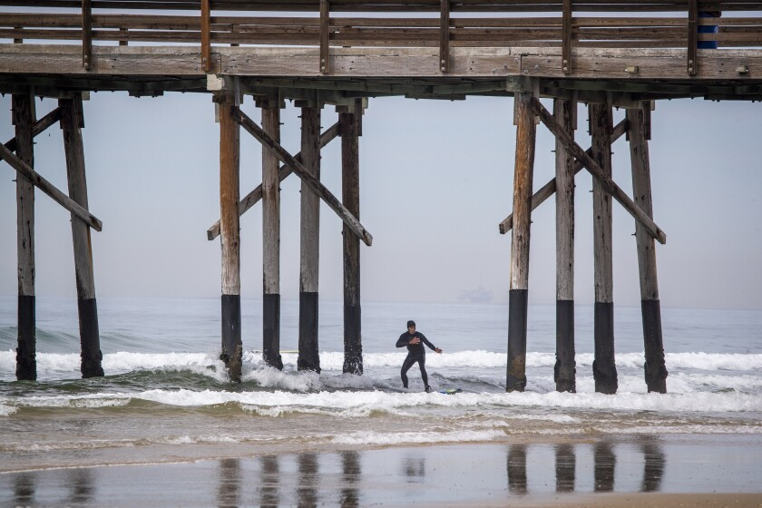 A surfer rides a wave near the closed Newport Pier on Tuesday.