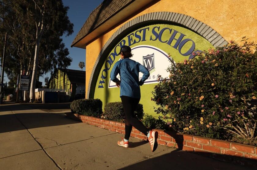 TARTAN CA MARCH 29, 2019 -- A jogger passes Woodcrest School in Tarzana Friday morning, March 29, 2