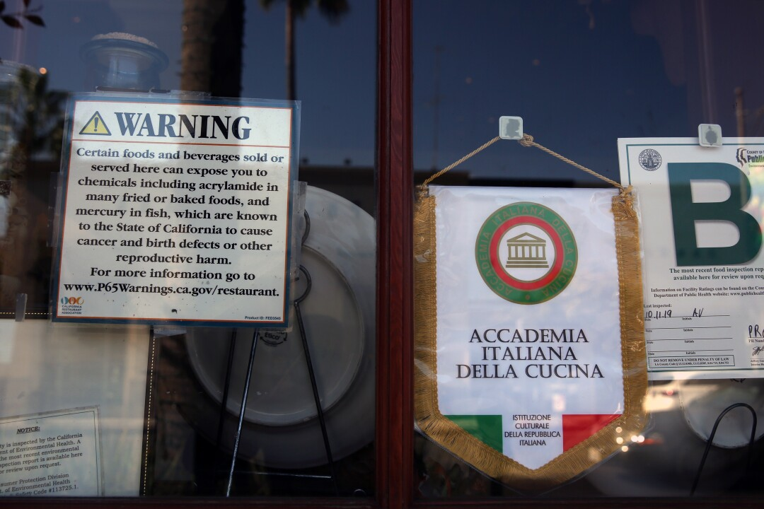 A Proposition 65 sign is prominently displayed on the window of an Il Fornaio Italian restaurant.