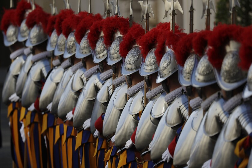 FILE - In this Thursday, May 6, 2021 file photo, Vatican Swiss Guards stand attention at the St. Damaso courtyard on the occasion of their swearing-in ceremony, at the Vatican. The Swiss government has decided to set up a dedicated embassy to the Vatican. Switzerland's ambassador to Slovenia is currently responsible for diplomatic relations with the Holy See. Switzerland has been diplomatically represented at the Vatican since 1991, though the post of ambassador was held by diplomats based in Bern, Geneva, Prague and since 2014, Ljubljana, Slovenia. Members of the world's oldest standing army provide ceremonial guard duty during papal Masses, stand watch at the Vatican gates and help protect Pope Francis. (AP Photo/Andrew Medichini, File)