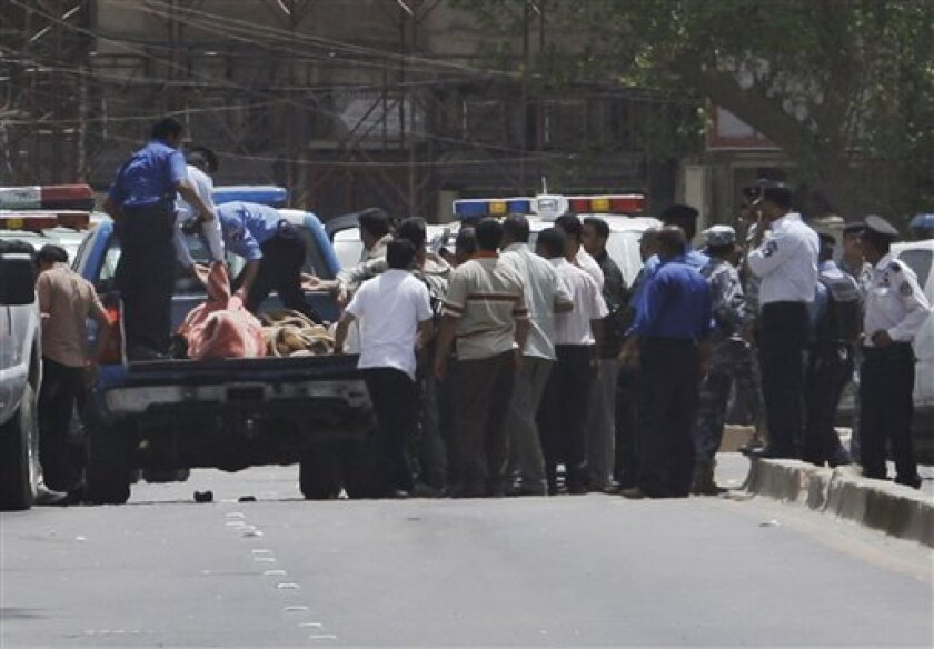 Iraqi police load victims killed in a bank robbery into a truck in central Baghdad, Iraq, Tuesday, July 28, 2009. Gunmen killed several security guards Tuesday during an early morning robbery at a bank in central Baghdad, an attack that appears to be the work of insurgents attempting to finance ope