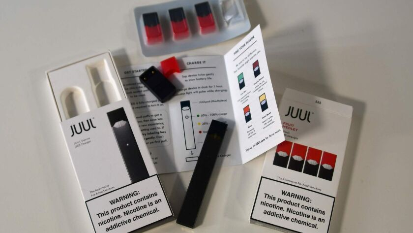 The contents of an Juul e-cigarette box, including vape pen and nicotine pods.
