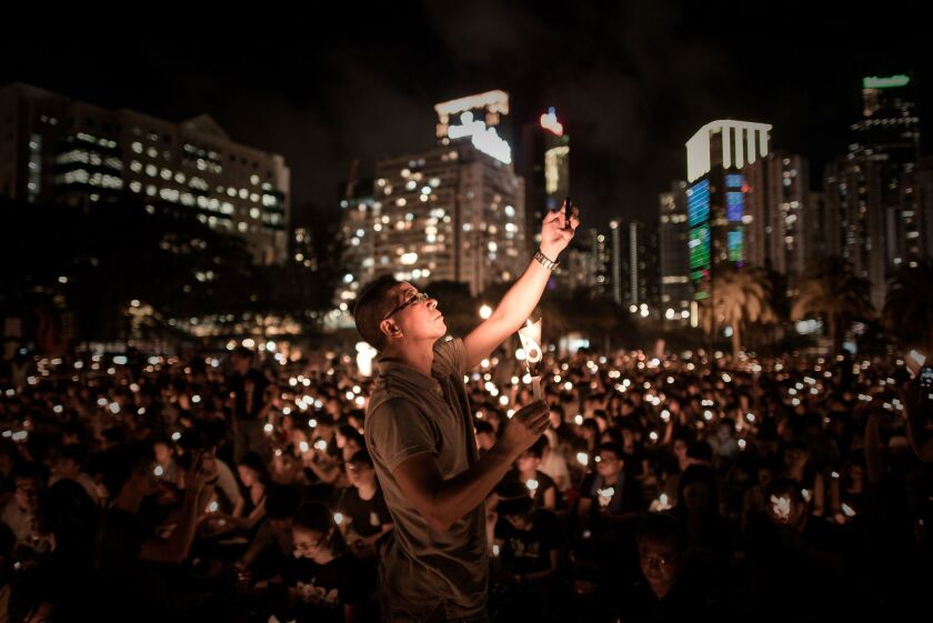 A man takes a picture with his phone as others hold candles at a vigil in Hong Kong to commemorate the 25th anniversary of the Tiananmen Square massacre in Beijing.
