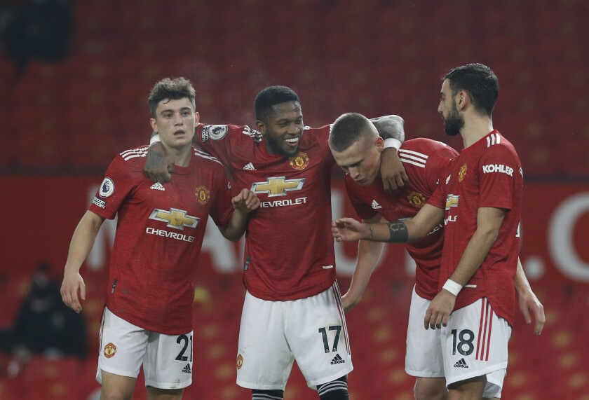 Manchester United's Scott McTominay, second right, celebrates with teammates after scoring his side's sixth goal during the English Premier League soccer match between Manchester United and Southampton, at the Old Trafford stadium in Manchester, England, Tuesday, Feb. 2, 2021.(Phil Noble/Pool via AP)