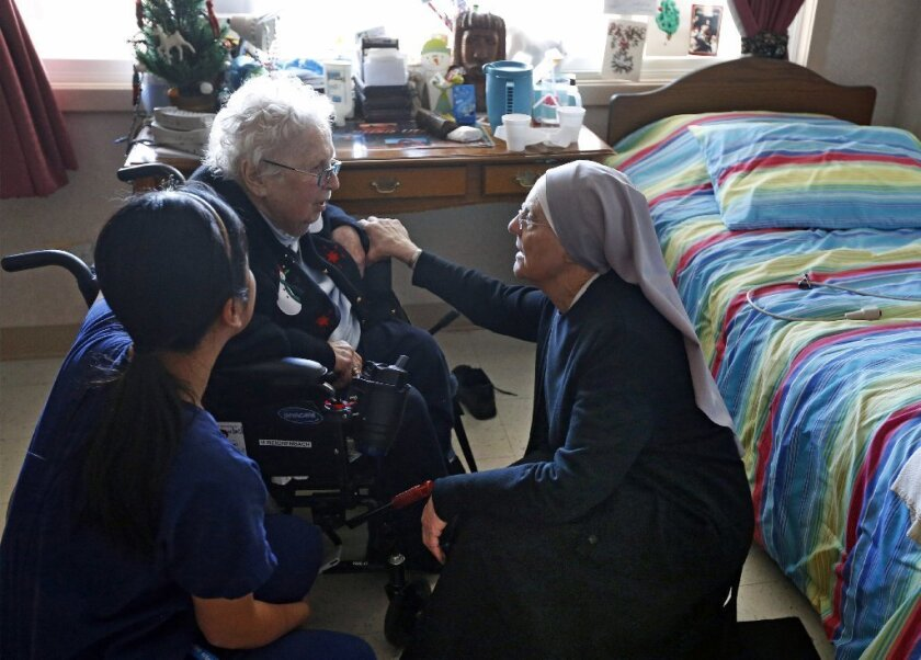 A nun and a nurse visit with a resident of a Little Sisters of the Poor home for the aged in Denver.