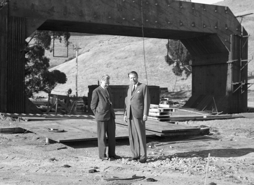 "Australian physicist Mark Oliphant, left, confers with Lawrence in the shadow of the massive 184-inch cyclotron magnet on Sept. 22, 1941. Image from the book ""Big Science"" by Michael Hiltzik."