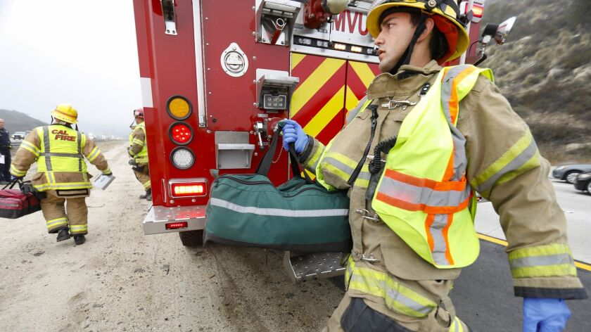 Cal Fire firefighters Trent Grinstead, background, left, and Anthony Lopez, right, arrive at a traffic collision on Interstate 15.