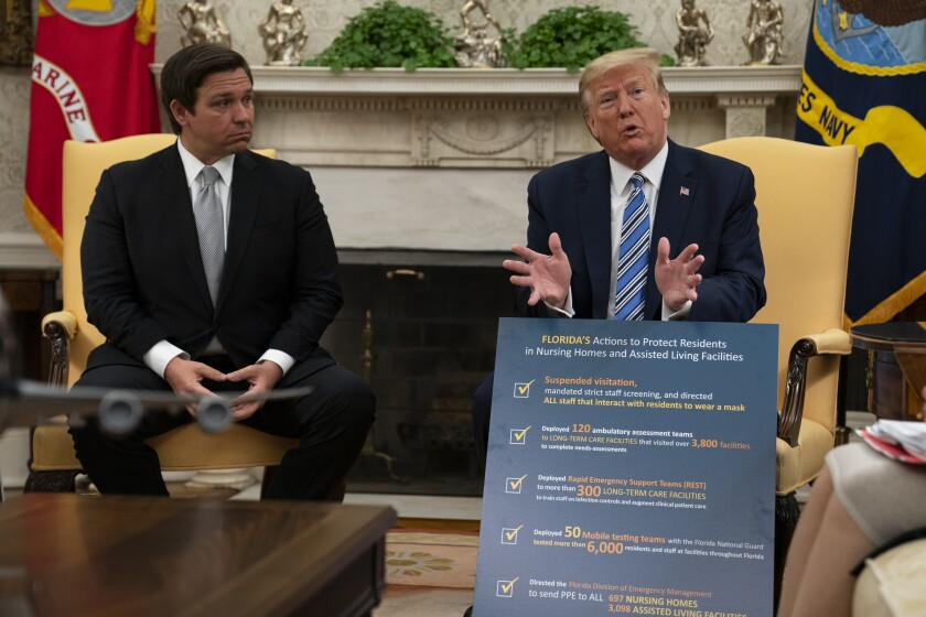 Florida Gov. Ron DeSantis listens as President Trump talks about the coronavirus response Tuesday at the White House.