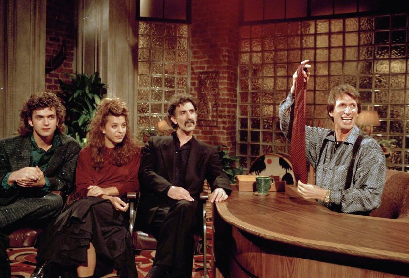 """FILE - In this Sept. 24, 1986 file photo, comedian David Brenner hosts avant garde fusion musician Frank Zappa, center, and his children, Dweezil, left, and Moon Unit, during a taping of Brenner's """"Nightlife"""" talk show in New York. Brenner holds a necktie given to Frank Zappa upon entering a restaurant earlier in the day. (AP Photo/David Bookstaver)"""