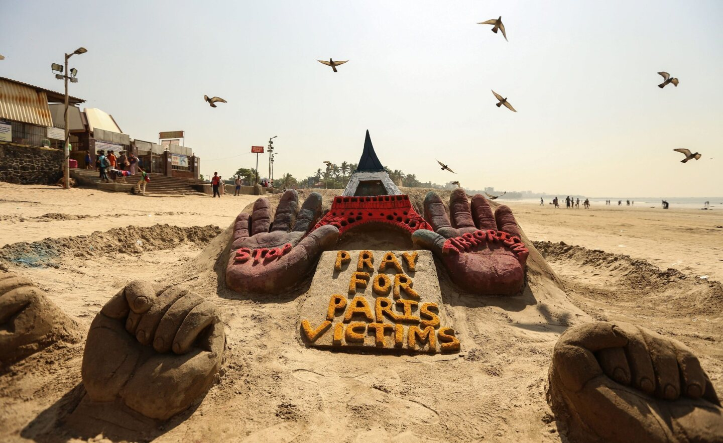 Pigeons fly over a sand sculpture paying tribute to the victims of the Paris terrorist attacks in Mumbai, India, on Nov. 20, 2015.