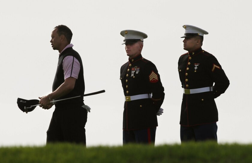 Day 1 of Farmers Insurance Open at Torrey Pines- SOUTH COURSE, Tiger Woods walks back to his caddy after greeting military personnel at the 14th. green of the South Course.