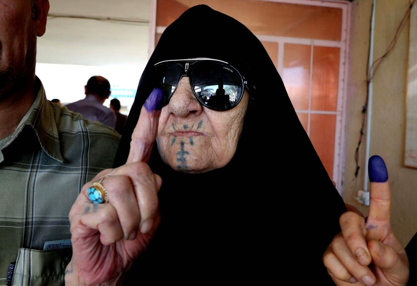 An Iraqi woman shows her ink-stained finger after voting at a polling station in Baghdad on Wednesday.