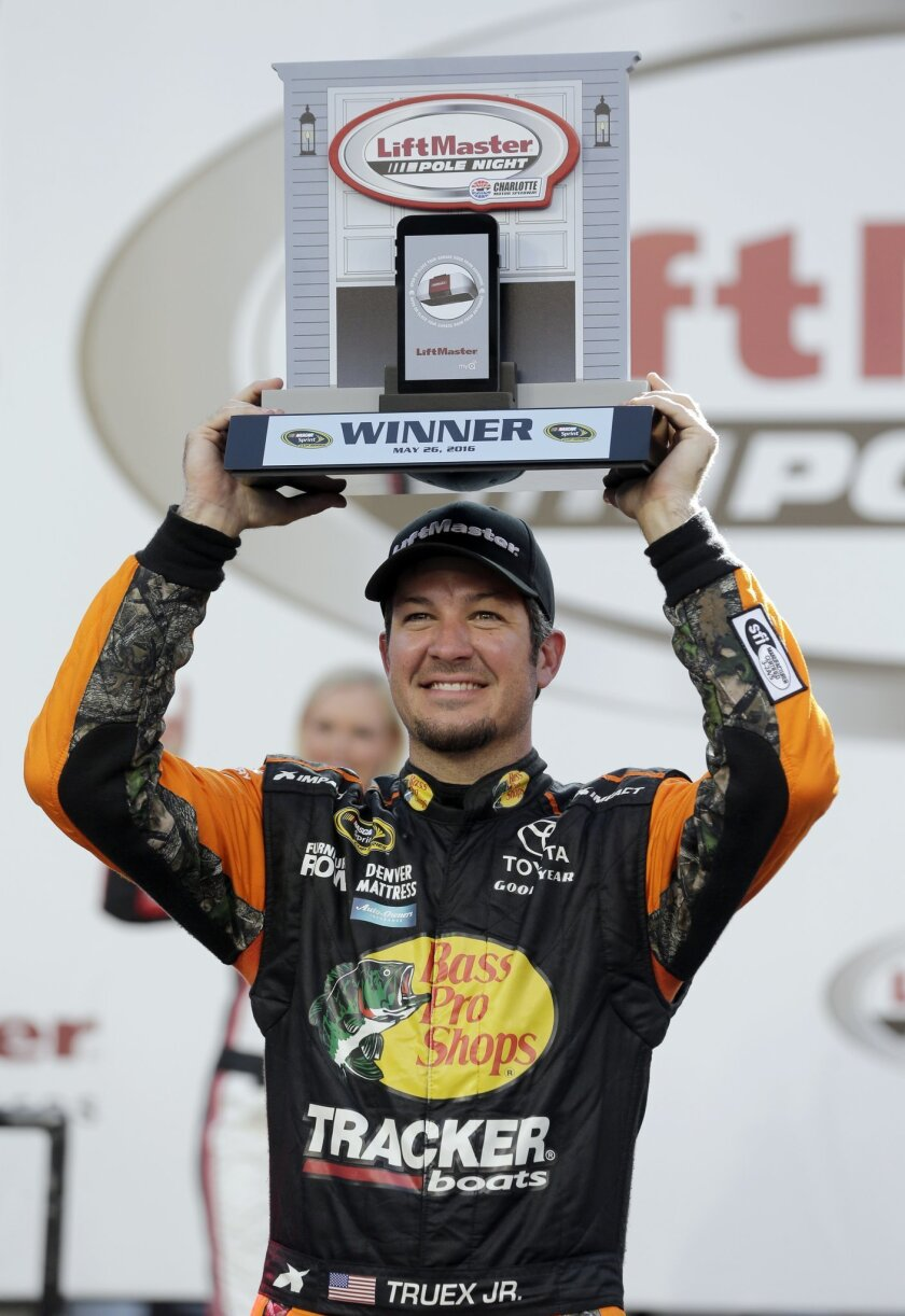 Martin Truex Jr. poses with the trophy in Victory Lane after winning the pole position for Sunday's NASCAR Sprint Cup series auto race at Charlotte Motor Speedway in Concord, N.C., Thursday, May 26, 2016. (AP Photo/Chuck Burton)