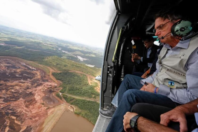 A handout photo made available by the Brazilian Presidency shows Brazilian President Jair Bolsonaro (R) as he sits inside a helicopter flying over the area affected by the dam burst near Brumadinho, Minas Gerais, Brazil, Jan. 26, 2019. EPA-EFE/FILE/Isac Nobrega /HANDOUT EDITORIAL USE ONLY