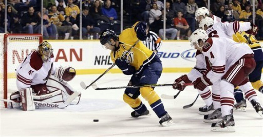 Nashville Predators center Mike Fisher tries to move between Phoenix Coyotes defenseman Zbynek Michalek (4), of the Czech Republic, and goalie Mike Smith (41) in the second period of an NHL hockey game, Thursday, Feb. 14, 2013, in Nashville, Tenn. (AP Photo/Mark Humphrey)
