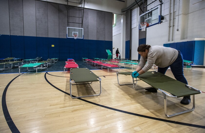 Salvation Army volunteer Christina Cuevas sets up cots for homeless people at Westwood Recreation Center in Los Angeles.