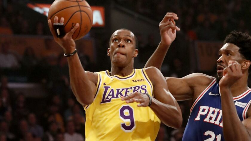 Lakers guard Rajon Rondo drives to the basket against 76ers center Joel Embiid during a game last season.