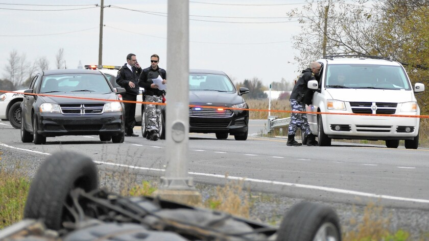 Investigators in Quebec work near an overturned car after two Canadian soldiers were hit Oct. 20. One of the soldiers died.