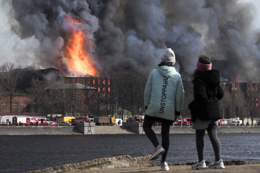 People look at smoke and flame rising from the Nevskaya Manufaktura textile factory founded by English merchant J. Thornton in 1841, in St. Petersburg, Russia, Monday, April 12, 2021. The emergencies ministry said the fire had broken out over several floors of the red-brick Nevskaya Manufaktura building on the Oktyabrskaya Embankment of the Neva River. (AP Photo/Dmitri Lovetsky)