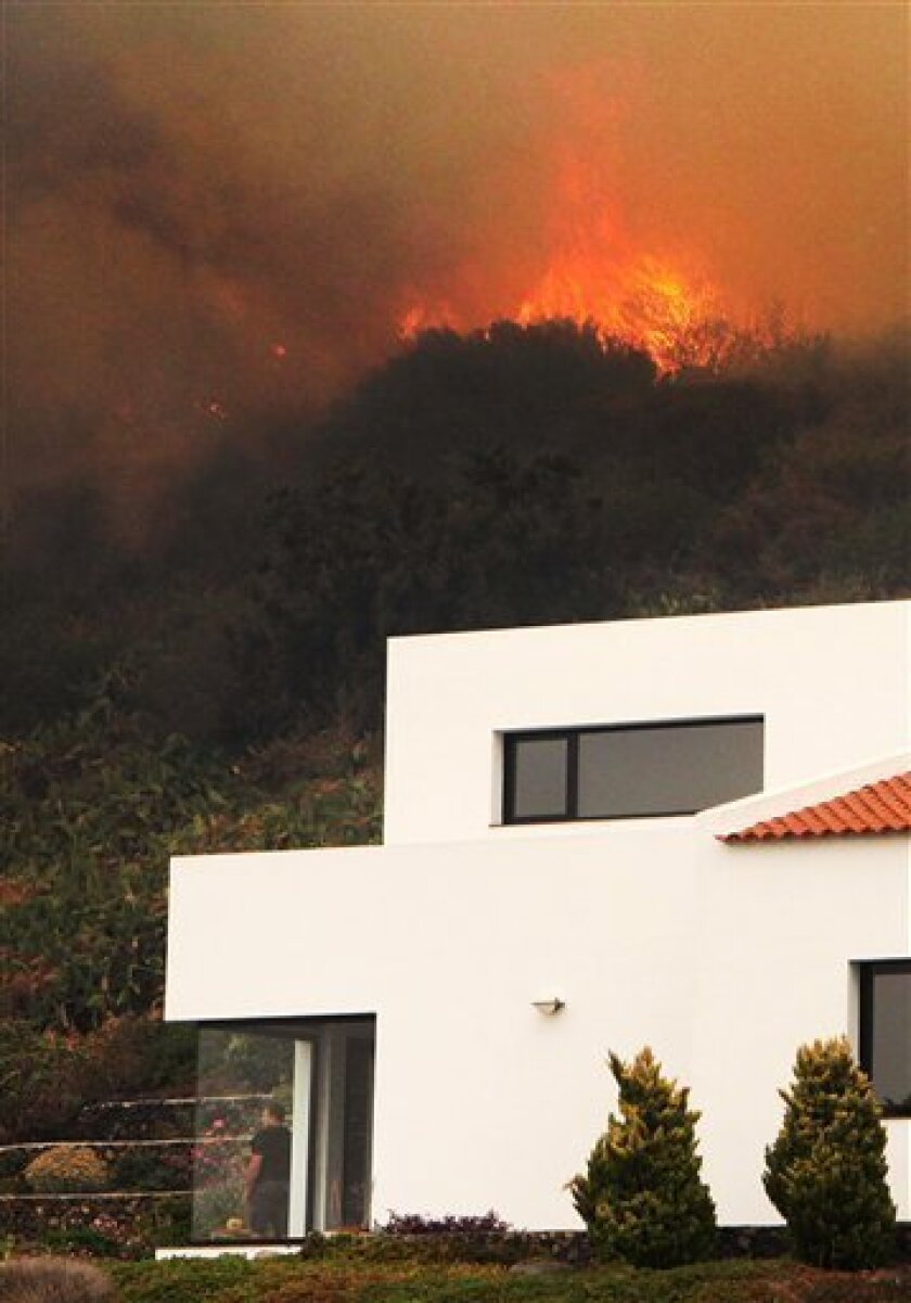In this photo taken on Saturday, Aug. 4, 2012, a man looks out from inside a house threatened by wildfire in La Palma, Spain. Wildfires fanned by fierce winds and high temperatures raged across Spain's Canary Islands of La Palma and La Gomera on Sunday. Flames are threatening to cut off La Gomera's phone communications and have forced the evacuation of hundreds of people. (AP Photo/Juan Arturo)