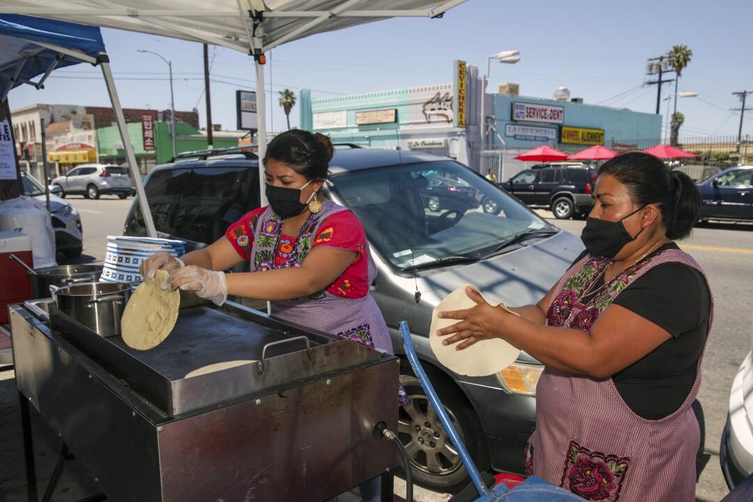 Two women prepare tortillas in a tent outside