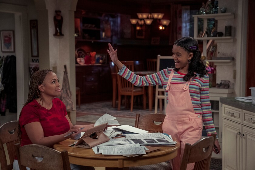 A woman with a pile of open books on a kitchen table, as her daughter attempts to high-five her