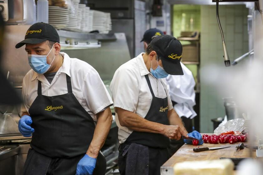 Masking-wearing employees prep food at Langer's Delicatessen-Restaurant