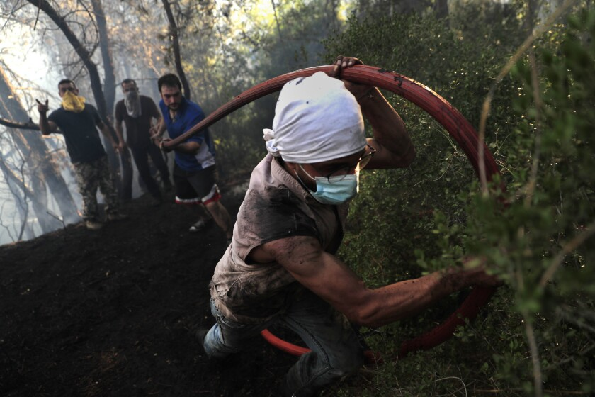 Civil defense workers extinguish a forest fire, at Qobayat village, in the northern Akkar province, Lebanon, Thursday, July 29, 2021. Lebanese firefighters struggled for the second day on Thursday to contain wildfires in the country's north that have spread across the border into Syria, civil defense officials in both countries said. (AP Photo/Hussein Malla)