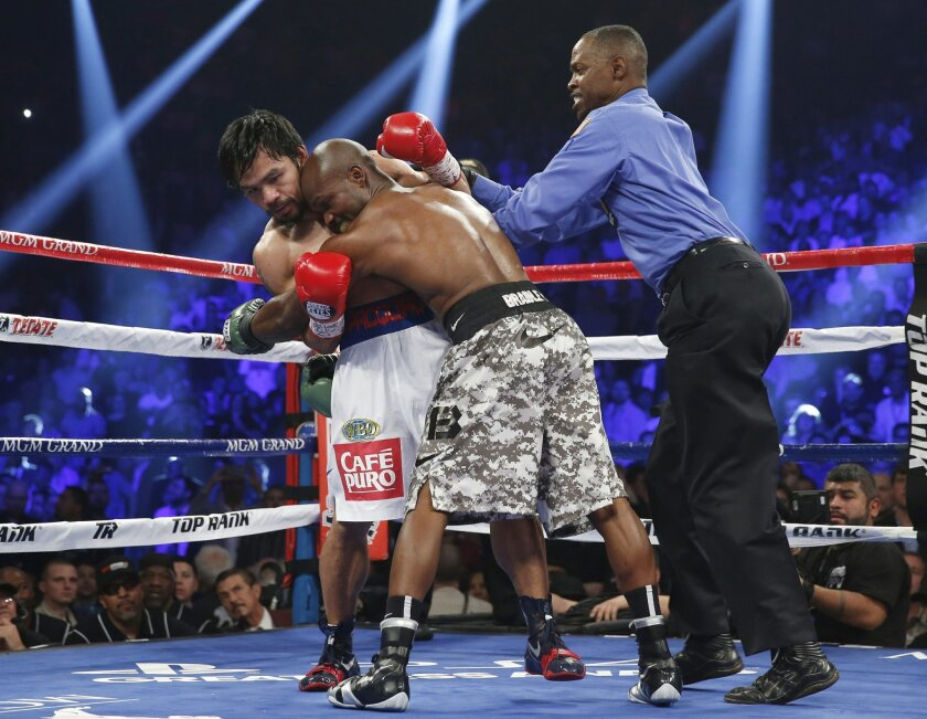 FILE - In this April 12, 2014, file photo, Timothy Bradley, center, hangs onto Manny Pacquiao, of the Philippines, as referee Kenny Bayless moves in to separate them during a WBO welterweight title fight in Las Vegas. Bayless will be the third man in the ring at the richest fight in boxing history.