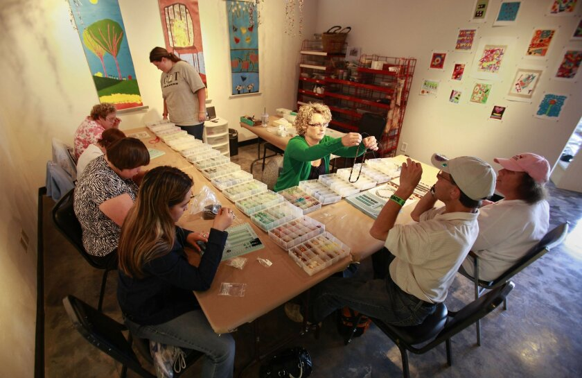 Barbie Bates works with the developmentally disabled students at Sophie's Gallery in El Cajon. [U-T file]