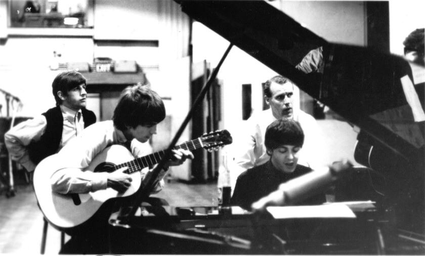George Martin in the recording studio with the Beatles.
