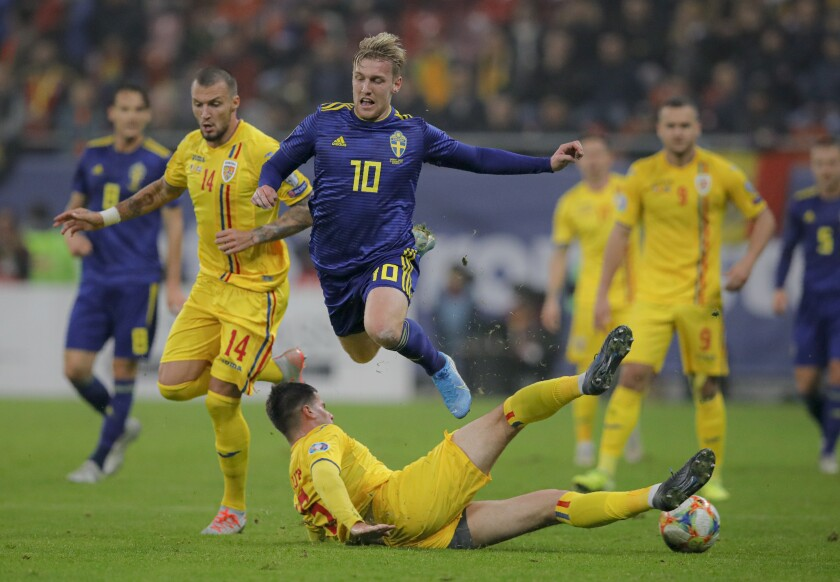 FILE - In this Friday, Nov. 15, 2019 filer, Sweden's Emil Forsberg. top, is tackled by Romania's Tudor Baluta during the Euro 2020 group F qualifying soccer match between Romania and Sweden on the National Arena stadium in Bucharest, Romania. (AP Photo/Vadim Ghirda, File)