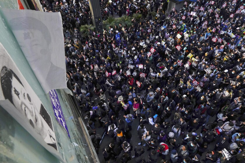 Pro-democracy protesters march past posters depicting Chinese President Xi Jinping on a pedestrian overhead bridge in Hong Kong on Dec. 8, 2019. Thousands of people took to the streets as an anti-government movement prepares to mark half a year of demonstrations.