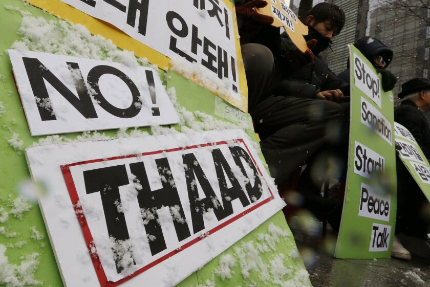 In this Feb. 16, 2016, photo, South Korean protesters hold banners during a rally to oppose the THAAD, or Terminal High Altitude Area Defense, system near the U.S. Embassy in downtown Seoul, South Korea. Furious about North Korea's recent nuclear test and long-range rocket launch, South Korea vows