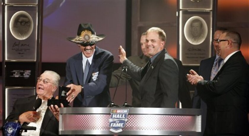 Maurice Petty, left, and Richard Petty, second from left, laugh with, from right, Mark Petty, Kyle Petty, Tim Petty and Ritchie Petty as they accept the induction of Lee Petty into the NASCAR Hall of Fame during a ceremony in Charlotte, N.C., Monday, May 23, 2011. (AP Photo/Terry Renna)