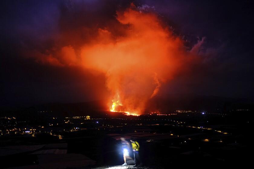 Dos personas caminan durante la noche mientras un volcán expulsa lava, en La Palma, Islas Canarias, el 25 de septiembre de 2021. (AP Foto/Daniel Roca)
