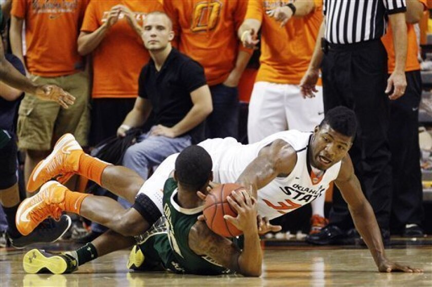 Oklahoma State guard Marcus Smart, right, reaches for the ball over South Florida's Anthony Collins in the first half of an NCAA college basketball game in Stillwater, Okla., Wednesday, Dec. 5, 2012. (AP Photo/Sue Ogrocki)