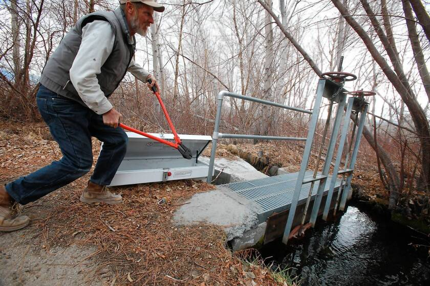 Frank Stewart shows off a bolt cutter that could be used in an emergency to cut a chain and padlock securing a gate on a ditch with water diverted from Pine Creek.