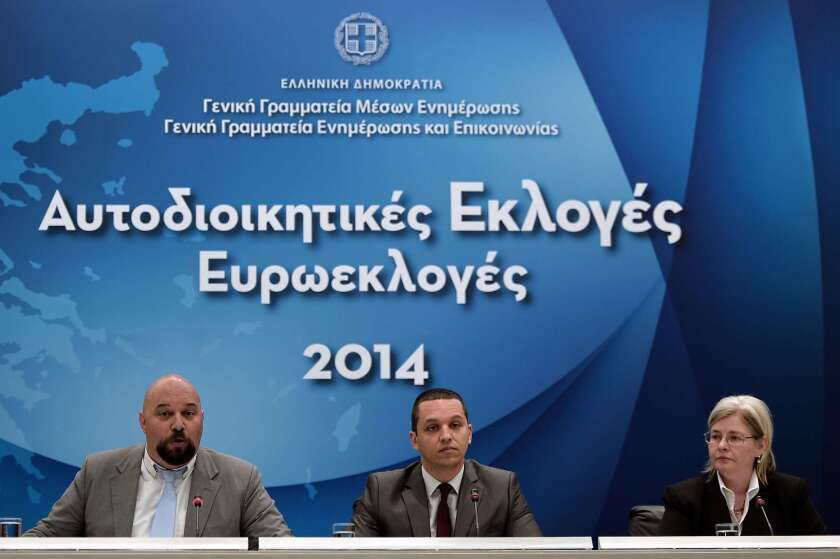 Golden Dawn lawmakers Ilias Panagiotaros, left, and Ilias Kasidiaris, center, at a televised news conference in Athens ahead of the May 25 EU elections; also attending was Eleni Zaroulia, wife of jailed leader Nikolaos Michaloliakos.