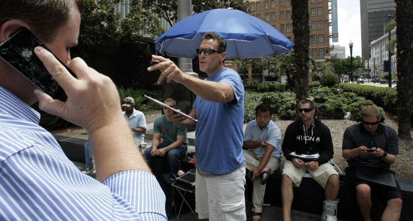 Jay Gafner, in sky blue and tan shorts, runs a trustee sale outside the downtown San Diego courthouse.