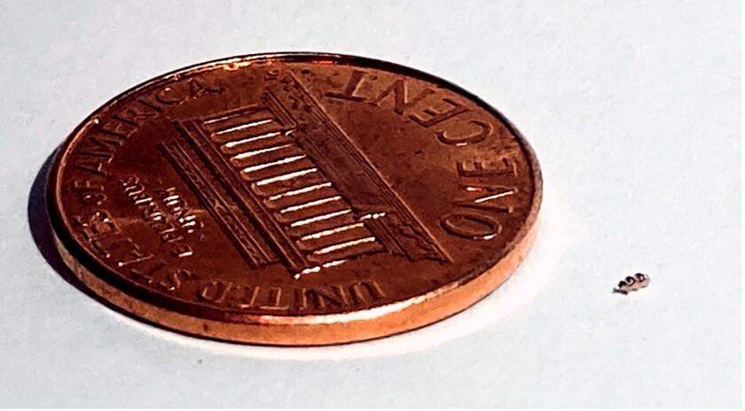 The helical Bionaut drug-delivery device, next to a penny for scale.