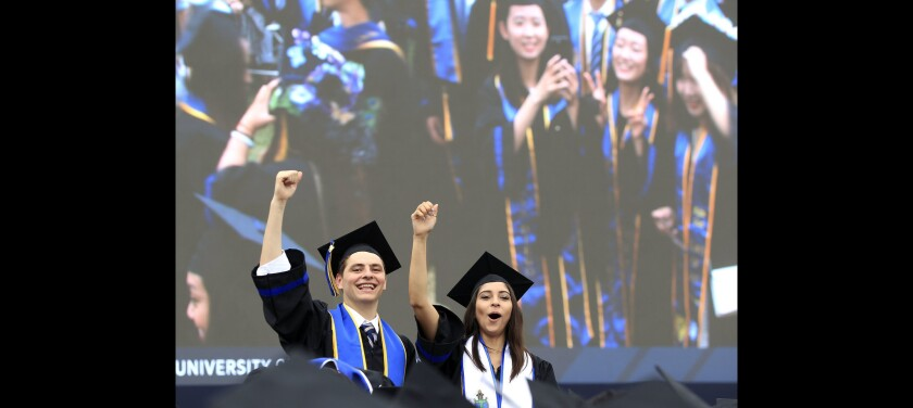 Two graduates hold up their fists after they and other graduates arrived at their seats.