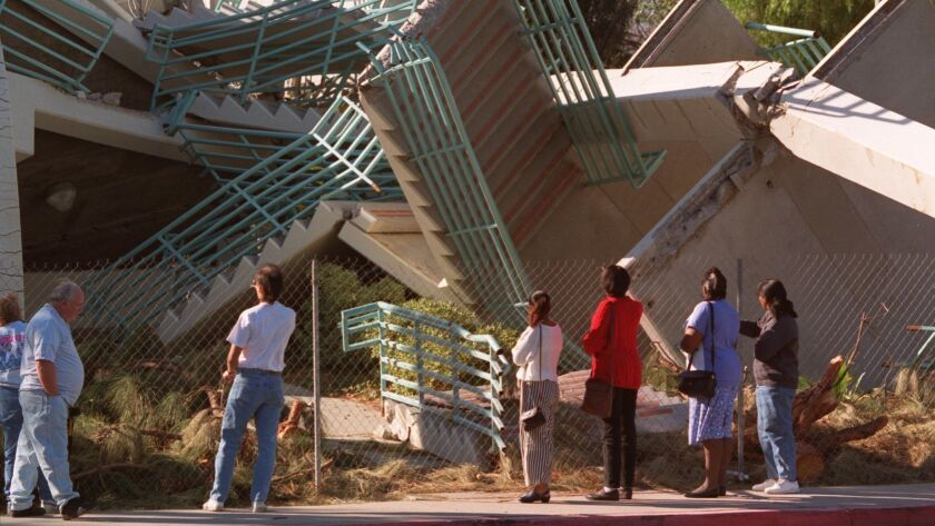 People look at a destroyed parking structure at Cal State Northridge in 1994 after the magnitude 6.7 Northridge earthquake.