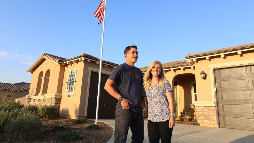 Josh and Kayleigh Hyink, former San Clemente residents, pose in front of the new home they recently purchased in the Riverside County community of Murrieta.