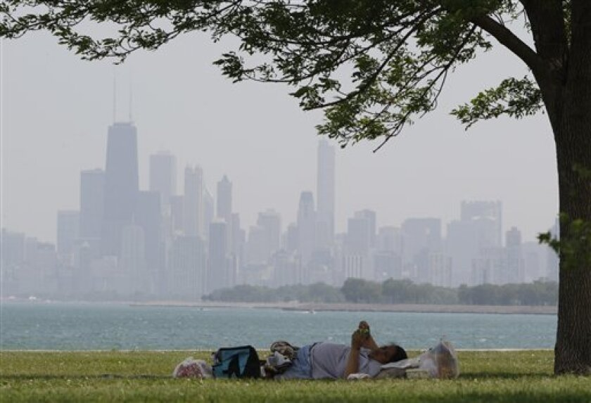 A woman rests during hot weather at Montrose beach in Chicago, Wednesday, June 8, 2011. Temperatures peak within a few degrees of the 97-degree 1933 record. Hottest early season spell in 34 years to break amid powerful, potentially severe storms Wednesday evening and night. (AP Photo/Nam Y. Huh)