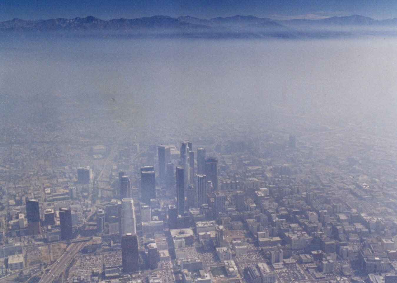 Aerial view of the downtown Los Angeles skyline covered in smog looking east towards the San Gabriel mountains in August 1990.