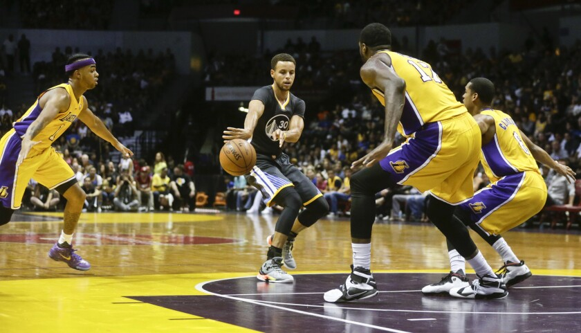 Golden State Warriors guard Stephen Curry splits the Lakers' defense with a fast-break pass during the first half of a preseason game on Oct. 17.