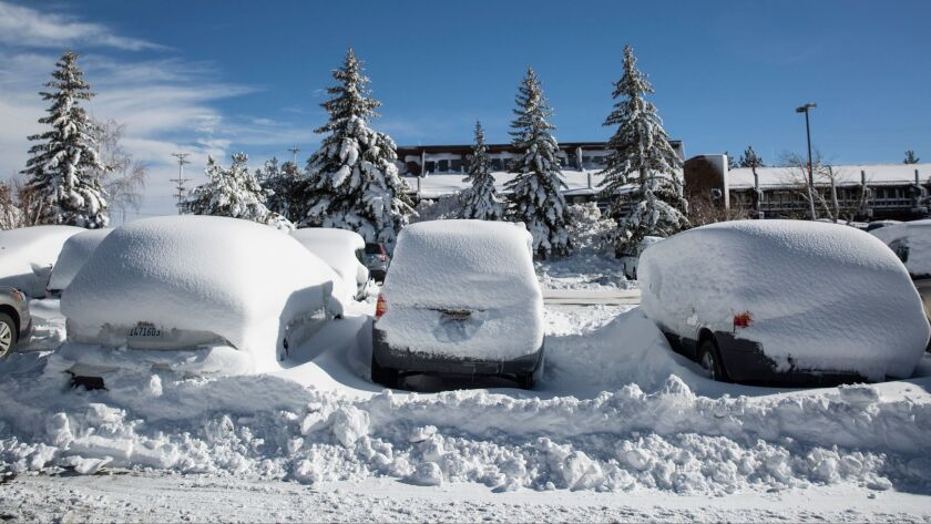 Snow covers vehicles in a parking lot in the Mammoth Lakes earlier this month.